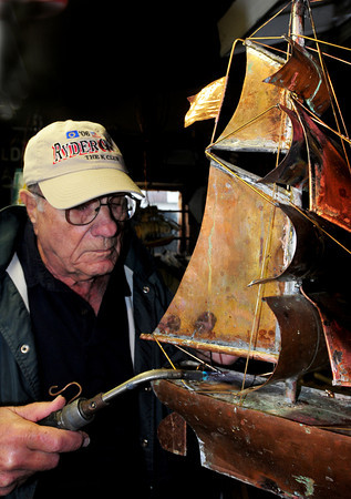 Newbury: Gene Palumbo works on a clipper ship in memory of his late son, Thomas, who served the area community for years including time as a state representative. The family will unveil the finished and gilded piece at Newburyport High--younger Palumbo's alma mater--next Wednesday; the family hoping to inspire students that they can do what they want in life. Bryan Eaton/Staff Photo