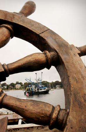 Newburyport: The Lisa Ann II framed by the ship's wheel of the fisherman's monument on Newburyport's Waterfront. Bryan Eaton/Staff Photo