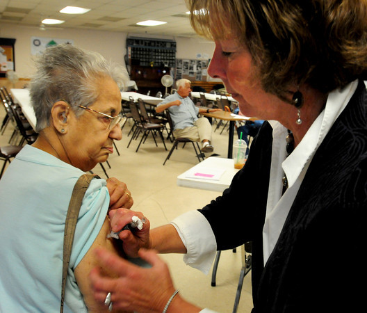 Salisbury: Public health nurse Cathy Vichill gives a flu shot to Gena Mical of Salisbury at the Hilton Center on Monday morning. Bryan Eaton/Staff Photo