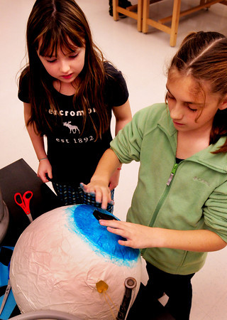 Salisbury: Jennie Larson, left, and Megan Jacobs, both 11, put the pupil in a giant paper mache eyeball at Salisbury Elementary School on Tuesday. Their class is creating a monster for the school's Halloween Parade on Monday. Bryan Eaton/Staff Photo