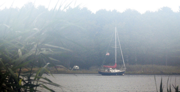 Amesbury: A sailboat sits in the early morning fog Saturday off Deer Island in Amesbury. JIm Vaiknoras/Staff photo