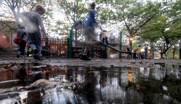 Newburyport: A puddle from Wednesday night rain reflects kids as they play at the Tot Lot on Inn Street in Newburyport Thursday. Jim Vaiknoras/Staff photo
