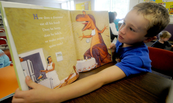 "Amesbury: Luke Buckley, a student in Sharon Nash's kindergaten class at Amesbury Elementary School reads ""How Do Dinosaurs Eat Their Food?"" in the schools library Thursday afternoon. Jim Vaiknoras/Staff photo"