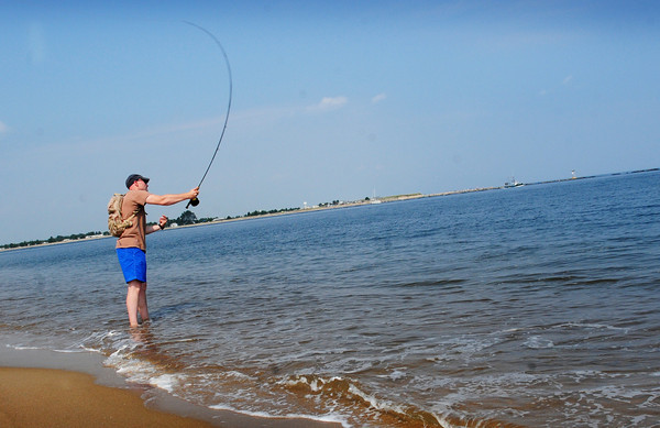 Newburyport: With his feet in the water, Drew Freisinger of Epping, N.H. casts his fishing rod in the Newburyport section of Plum Island. The beaches have reopened after being closed for high levels of bacteria. Bryan Eaton/Staff Photo