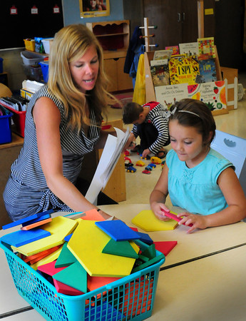 Amesbury: Isabelle Levasseur, 5, gets familiarized with her new classroom from her kindergarter teacher Sharon Nash at Amesbury Elementary School yesterday. It was the first day of school in Amesbury, though only orientation for kindergartners who start today. Bryan Eaton/Staff Photo