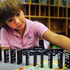 "Amesbury: Abigail Hutchings, 8, lines up dominoes as classmates next to her do the same to knock over at the Cashman School in Amesbury yesterday afternoon. She was in Victoria Fitzpatrick's second grade class in ""Monday Magic"" where children explore different pursuits and interact with each other in common interests in a fun way. Bryan Eaton/Staff Photo"