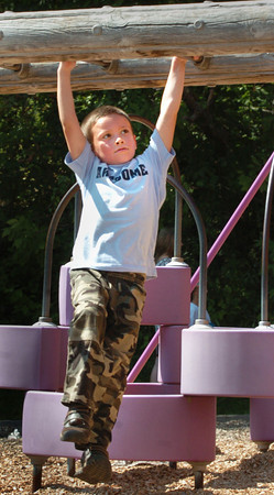Amesbury: James Phipps, 6, moves along the monkey bars at Amesbury Elementary School on Tuesday during recess in the summerlike weather. Bryan Eaton/Staff Photo