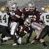 Amesbury: Amesbury's Stephen Deas goes down as teammates Dalante Castle, left, and Dan Norton (53) block North Reading defenders. Bryan Eaton/Staff Photo