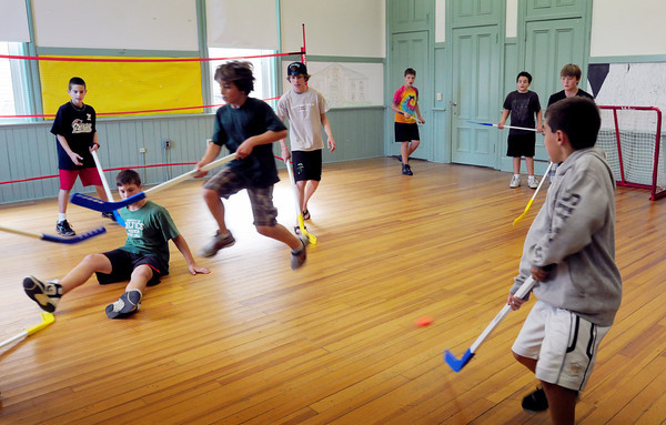 Newburyport: Children play floor hockey at the Kelley School Drop-In Center which has seen an increase in participation. Bryan Eaton/Staff Photo