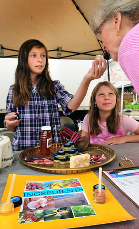 Newburyport: Linda Nielsen of Newbury smells a sample of lip balm from Kelsey Logan, left, and Emme Stroman, both 10 of Newburyport at the Farmer's Market yesterday. With the help of Natural Touch owner, Anne Upton, the two make the balm from ingredients they get at the Farmer's  Market from honey and beeswax to beets. Bryan Eaton/Staff Photo