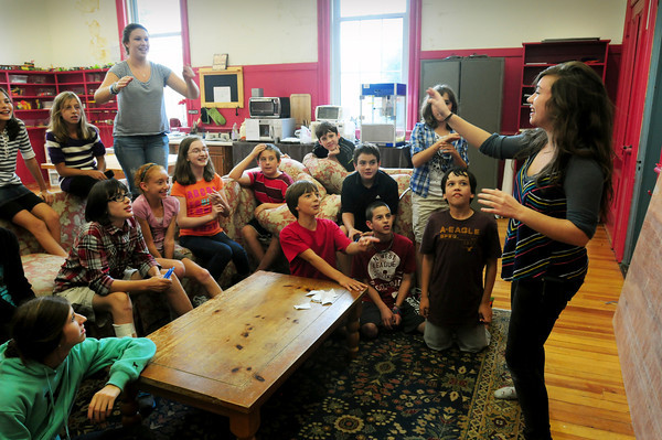 """Newburyport: Children at the Kelley School Drop-In Center play a game of charades recently. Isa Maginnis, right, tries to portray """"The Little Mermaid."""" Bryan Eaton/Staff Photo"""