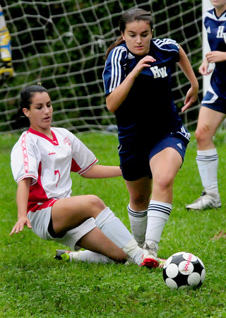 Amesbury: A Hamilton-Wenham player moves past Amesbury's Jeanine Fatal, left, yesterday at the Cashman School field. Bryan Eaton/Staff Photo
