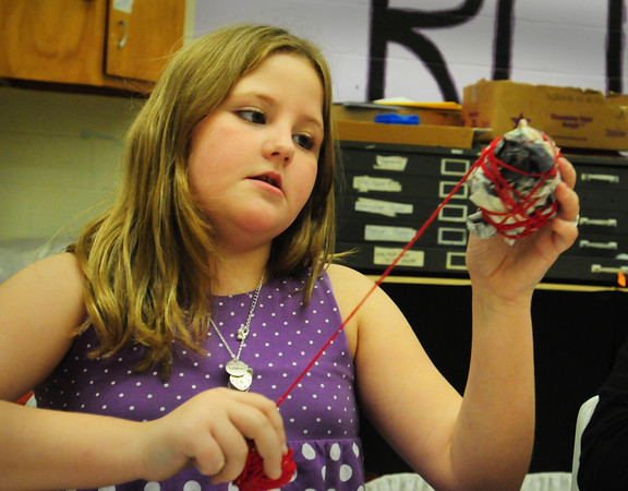 Salisbury: Chloe Hynes, 8, of Salisbury winds red yarn around a ball of newspaper at the Boys and Girls Club yesterday afternoon. The children in the art room were making pumpkins and apples out of the material. Bryan Eaton/Staff Photo