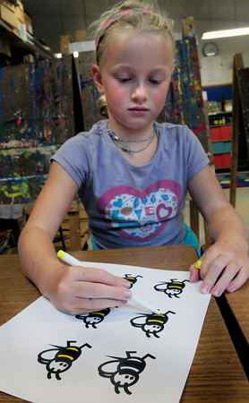 """Newburyport: Avery Keller, 7, colors in bumblebees for the """"Busy Bees of the Bresnahan School"""" in Pam Jamison's art class. The bees are cut up and put into a teacher's box and when a student does something special like """"be nice, be smart, be helpful"""" etc., their teacher puts a bee with their name on a bulletin board. Bryan Eaton/Staff Photo"""