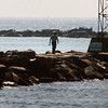 Salisbury: A fisherman looks for a suitable spot to cast his line on the north jetty of the Merrimack River at Salisbury Beach State Reservation on Tuesday morning. Bryan Eaton/Staff Photo