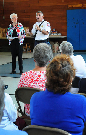 Newburyport: Newburyport fire Chief Stephen J. Cutter, with Fran Monroe, chairman of the Newburyport Council on Aging, talks to senior citizens about keeping emergency medical information, including medications, in an obvious place, like on the refrigerator for emergency personnel to easily find. They were at a Senior Safety Day at the Salvation Army building sponsored the the council, Newburyport Police and Fire Departments. Bryan Eaton/Staff Photo