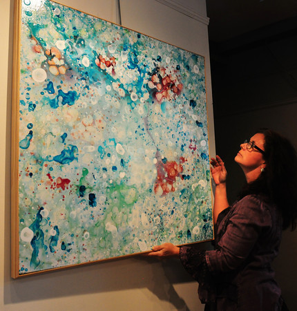 Newburyport: Kathy Staab of the Newburyport Art Association hangs the Best of Show. Bryan Eaton/Staff Photo