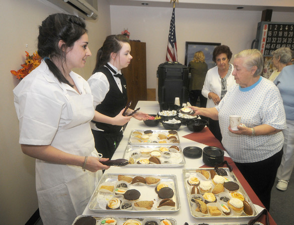Amesbury: Sarah Dubouis of Haverhill and Regan Milmore of North Andover serve pasteries to Heritage Tower resident Annetta Edgerly Friday afternoon. Sarah and Regan are culinary arts students at Whittier and along with other student served lunch to the residence. Jim Vaiknoras/Staff photo