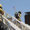 Newburyport: Firefighers vent the roof at the scene of a fire on Olive Street in Newburyport Sunday. Jim Vaiknoras/Staff photo