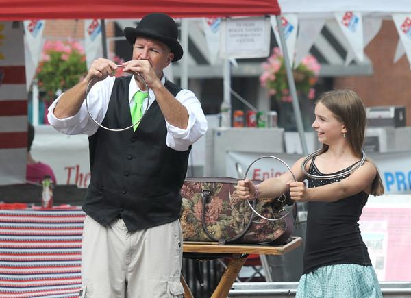 Newburyport: Silja Steinmann, 11, of Newburyport helps out magician Joe Howard in Market Square at the Newburyport Labor Day Festival. Jim Vaiknoras/Staff photo