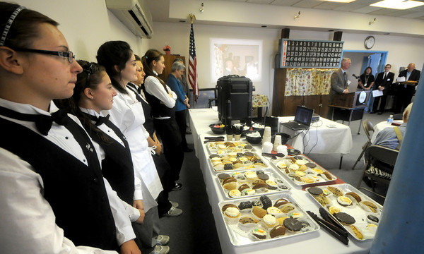 Whittier Tech culinary arts students Jackie LeBlanc, Christine Barton, Sarah Dubois, Brittany Johnson and Brittany Kuse look on as Mayor Thatcher Kezer during teh 10th anniversary of the Supportive Housing Initative at the Heritage Towers. Jim Vaiknoras/Staff photo