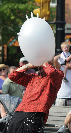Newburyport: Street performer Figo blows up a rubber glove till it pops while it's on his head during his performance at the Newburyport Labor Day Festival in Market Square Sunday. Along with the rubber glove gag Figo also swallowed balloons, layed down on broken glass, and performed various other dangerous and entertaining high jinx. Jim Vaiknoras/Staff photo