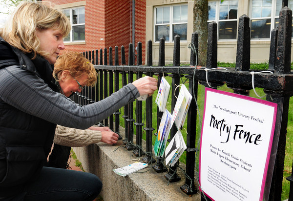 "Newburyport: Lucia Greene, left, and Susan Gaylord attach poems of fourth grade students to the ""Poetry Fence"" outside the Newburyport Public Library to promote this weekend's Literary Festival. Bryan Eaton/Staff Photo"