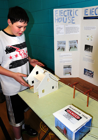"Merrimac: Andrew Buzzell, 12, shows off models of a home connected by transmission lines to a power plant at the science fair at the Donaghue School in Merrimac. His project was ""What is the Power of Electricity."" Bryan Eaton/Staff Photo"