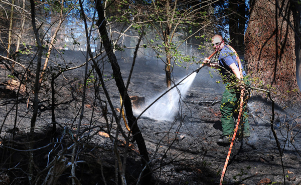 Byfield: A firefighter looks for hot spots among the charred undergrowth during a brush fire on Middle Road in Byfield yesterday afternoon. The dry conditions will be getting relief over the weekend as up to two inches of rain is expected. Bryan Eaton/Staff Photo