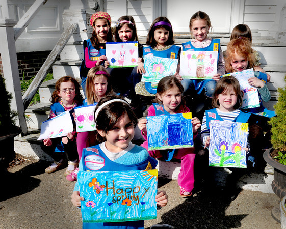 "Newburyport: Members of Daisy Troop 85333 in Newburyport have made designs which have been made into greeting cards to be sold at the Emma Andrews Library as a fundraiser to buy children's books. In front with her ""happy spring"" drawing, Ava Maglio is flanked by her friends. Row one, from left, Tara Sullivan, Shannon Brock, Kayla Whitty and Katie Conway. Row two, from left, Carmella Mastrangelo, Rita Cachalane, Emma Cowles, Taytum Bernard, Julianna Cowles, hidden, and Carly McDermott. Bryan Eaton/Staff Photo"