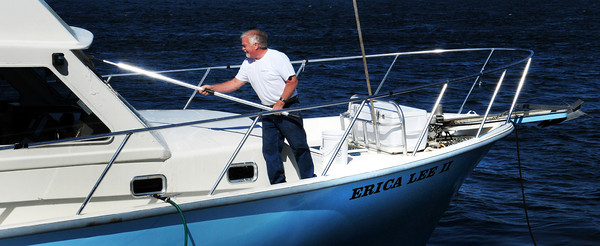 Newburyport: Bob Yeomans cleans off the windows of his charter boat Erica Lee II yesterday afternoon on the Newburyport waterfront after a recent trip out. The boat is used in the summer months to take children out to learn about marine life. Bryan Eaton/Staff Photo