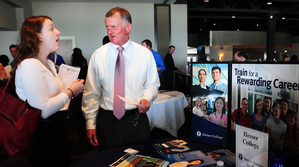 Salisbury: Lauren Chappell of Haverhill asks a question to Steve Emberley, admissions representative at Hesser College. They were a the Valley Works Jobs Fair at Blue Ocean Music hall yesterday morning. Bryan Eaton/Staff Photo
