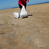 Salisbury: Robin Weisenstein, manager of Michael's Oceanfront Hotel at Salisbury Beach, picks up trash in front of the building yesterday afternoon. She filled five of these white bags one day after a busy weekend. Bryan Eaton/Staff Photo