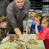 Newburyport: Artist Robert Rossell shows students a piece of clay that he imprinted with sea shells and a rubber lizard at the Brown School on Monday. The children then made their own designs the are to be oven-dried at home, then back to school to be painted in the project sponsored by the Newburyport Education Foundation. Bryan Eaton/Staff Photo