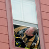 Newburyport: A firefighter calls instruction out of an upper story window at <br /> the scene of a fire on Prospect Street in Newburyport Sunday. Jim Vaiknoras/staff photo