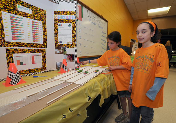 Newburyport: Second graders Meagan Murry and Madeleine Rubino use toy cars and different texured surfaces to demostrate the effects of friction on motion  at the Besnahan Elementary Science Fair Thursday night. Jim Vaiknoras/staff photo