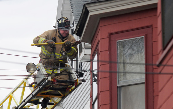 Newburyport: A firefighter removes molding as he searches for hot spots at <br /> the scene of a fire on Prospect Street in Newburyport Sunday. Jim Vaiknoras/staff photo