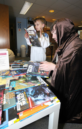 Amesbury: Ryan Collins, dressed as a Clone Trooper, and Scituate Llibrarian Petet Struzziero, dressed as Obi Wan Kenobi ,look at the coolection of Star Wars books during a Star Wars Symposium at the Amesbury Library Saturday. The event , put on by Struzziero, featured a trivia contest, video games, and a costume contest. JIm Vaiknoras/staff photo