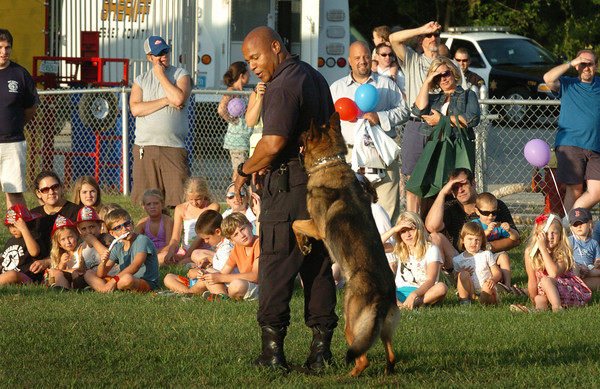 West Newbury: Sgt. Derik Beasely of the Essex County Sheriff's Department gives a canine demonstration with Ruger at West Newbury's first Night Out on Tuesday. West Newbury Police Chief Lisa Holmes as happy with the turnout and hopes to expand next year. Town departments had vehicles for residents to check out along with activities for youngsters including a dunk tank. Bryan Eaton/Staff Photo