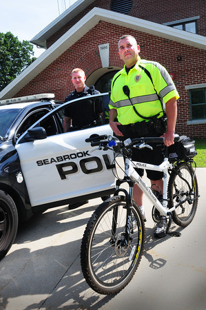 Seabrook: Seabrook patrolman Justin T. Murphy, left, and Sgt. Jason Allen show off one each of new cruisers and bicyles the department has purchased. Bryan Eaton/Staff Photo
