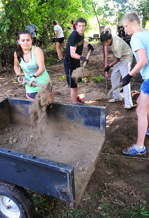 Newbury: Cast members of Up With People dig out a spot for a sandbox behind the First Parish Church in Newbury on Tuesday afternoon. They were doing a community service project at the church's Secret Garden Preschool. Bryan Eaton/Staff Photo