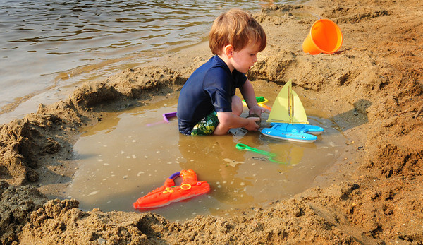 Amesbury: Mather Sekelsky, 3, of Amesbury plays with his sailboat in a pond he and his friends made at Lake Gardner Beach on Friday afternoon. Bryan Eaton/Staff Photo