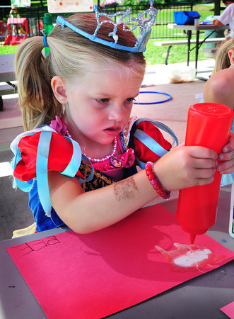 Amesbury: Dressed as Snow White, Becca Hussey, 4, has a hard time squeezing one bottle of colored sand onto glue to create a beach scene at the summer program at Amesbury Town Park. It was dress up day and the youngsters were asked to show up in costumes they like. Bryan Eaton/Staff Photo