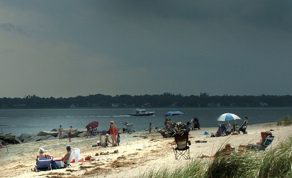 Salisbury: Dark clouds formed to the west in view of these sunbathers at Salisbury Beach State Reservation yesterday afternoon, with showers arriving a couple hours later. There is still a slight chance of showers today as the air remains muggy. Bryan Eaton/Staff Photo