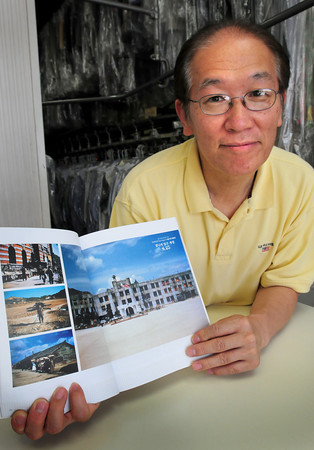 Newburyport: Newburyport's Jim Maguire who fought in the Korean Conflict took many color photos while stationed there. He gave his photos to Ko Tom, pictured, who owns a dry cleaning business in Port Plaza who helped to get a photo exhibit of Maguire's work published. Bryan Eaton/Staff Photo