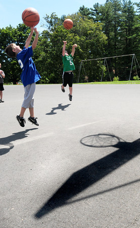 "Amesbury: Timmy Hussey, 7, left, and Aidan Donovan, 6, throw basketballs at Amesbury Town Park on Monday afternoon. They were in a game of ""Knockout"" in the Amesbury Recreation Department's Summer Program which ends next week.Bryan Eaton/Staff Photo"