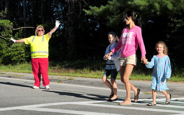 Merrimac: Sweetsir School crossing guard Donna Carr stops traffic as Joanna Goodwin walks her daughters to the Merrimac school. Lia, 7, left is going into the second grade and Gwen won't start for another year. Bryan Eaton/Staff Photo