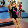 Newburyport: Kasey Hogg, 9, of Kensington, NH works out on the uneven bars at All-Around Gymnastics. Bryan Eaton/Staff Photo