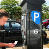 Newburyport: Roy Valaitis of Salem grabs his ticket from a parking kiosk in the Green Street parking lot in downtown Newburyport. Some think the paid parking has cost business owners customers, but the program has made the city some money. Bryan Eaton/Staff Photo