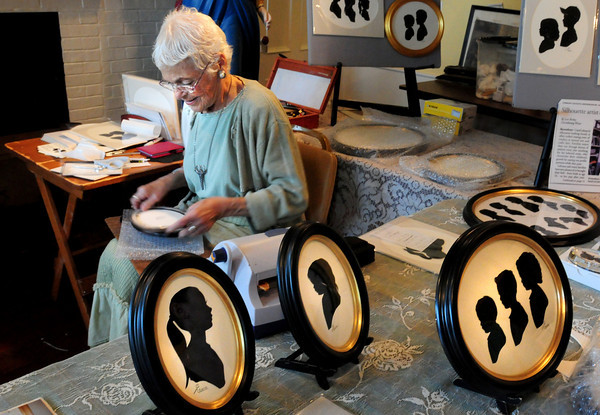 Newburyport: Silhouette artist Carol Lebeaux frames some of her work from earlier yesterday while waiting for other customers at the Cushing House Museum. Bryan Eaton/Staff Photo